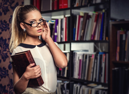 Female student at the library holding a book photo