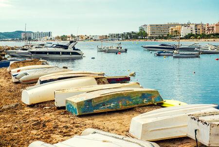 Old boats on the empty beach of Ibiza   Balearic Islands, Spain photo
