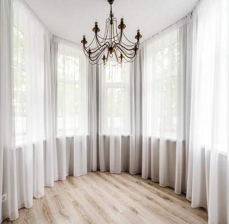 Interior Habitación elegante con suelo de madera, cortina blanca y araña Foto de archivo