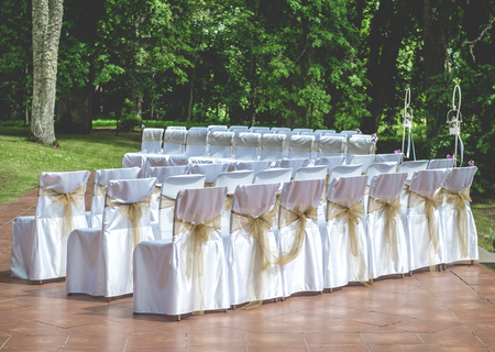 White Wedding Chairs With Brown Bows Outdoors Stock Photo