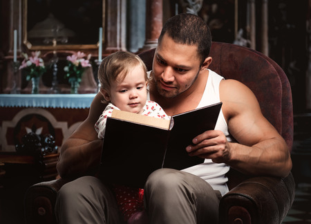 Father reading book to daughter photo