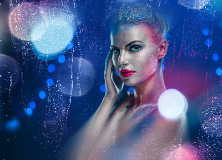 Beautiful woman with creative bright make-up over glowing lights background  photo