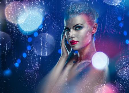 Schöne Frau mit kreativen hellen Make-up auf glühenden Lichter Hintergrund Standard-Bild
