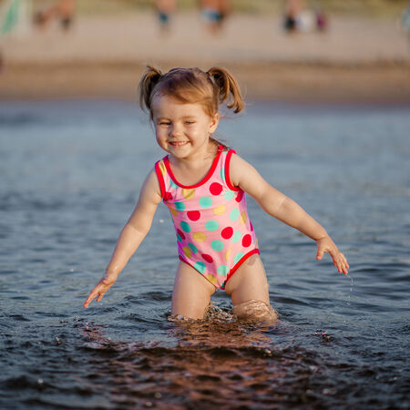 Adorable baby girl playing with a water in the sea photo