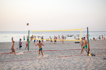 jurmala: Jurmala, Latvia-July 30, 2014: Group of friends playing volleyball on the beach on a hot summer day, 30C outside on July 30, 2014