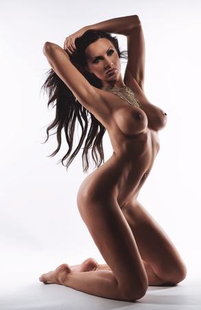 tetas: Morena desnuda sobre fondo blanco Foto de archivo