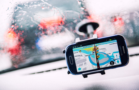 Smart phone with a Waze GPS navigator on the screen. Waze is one of the worlds largest community-based traffic and navigation apps