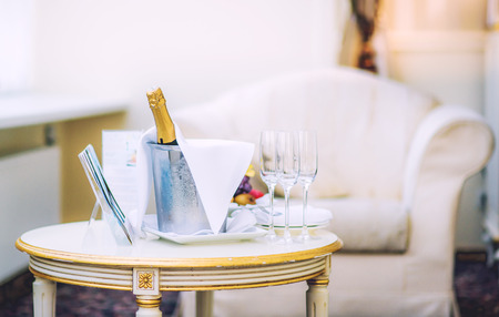 hotel suite: Bottle of champagne and glasses on a table in the hotel room