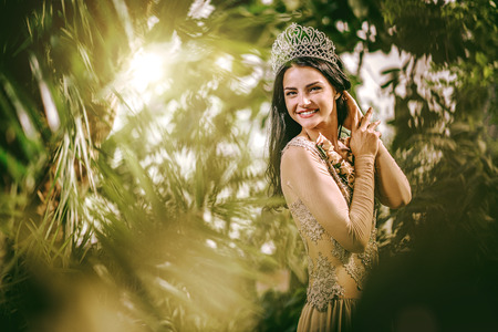 Gorgeous lady in evening dress and with tiara on a head posing in a forest