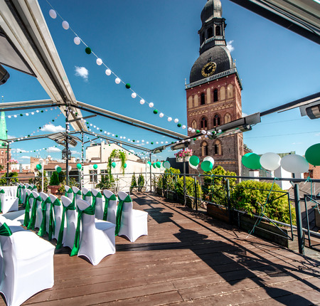 White chairs with green ribbon on a terrace is ready for a wedding ceremony