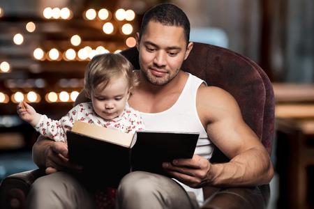 niños leyendo: Padre que lee el libro a la hija