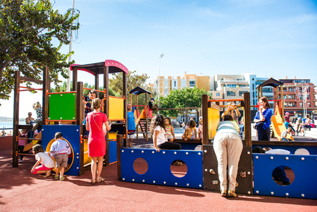 arona: Tenerife, Canary Islands- December 28, 2014: Children playing in the playground in Los Cristianos. Los Cristianos is a popular tourist resort in Tenerife