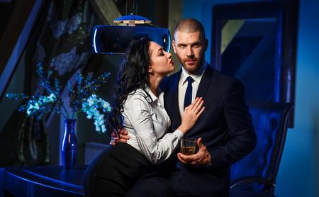Couple indoors. Sensual brunette and handsome businessman. Office romance concept Standard-Bild