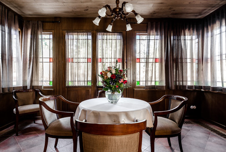 dining table and chairs: Contemporary dining room design. Glassed room with wooden ceiling, comfortable chairs, round table with white tablecloth and bouquet of flowers Stock Photo