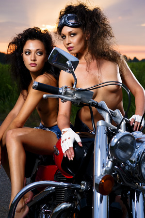 Two sexy young woman sitting on a motorcycle outdoors photo