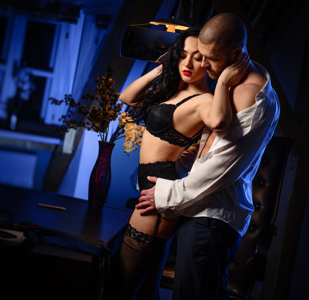adult sex: Couple indoors. Sensual brunette in black lingerie and handsome man. Office romance concept