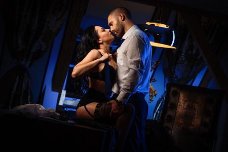 Paar binnenshuis. Sensuele brunette in zwarte lingerie en knappe man zoenen. Kantoor romantiek begrip Stockfoto