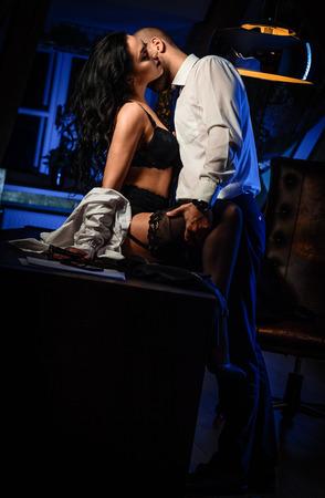Couple à l'intérieur. Brune sensuelle en lingerie noire et un homme beau embrasser. Bureau concept de roman Banque d'images - 38452869