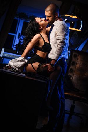 sexo: Pareja en el interior. Morena sensual en ropa interior negro y guapo besos. Concepto romántico de la oficina Foto de archivo