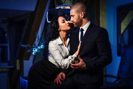 young sex: Couple indoors. Sensual brunette seduces handsome businessman. Office romance concept