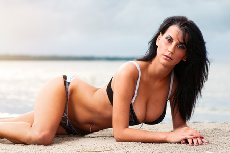 Seductive brunette relaxing on the beach photo