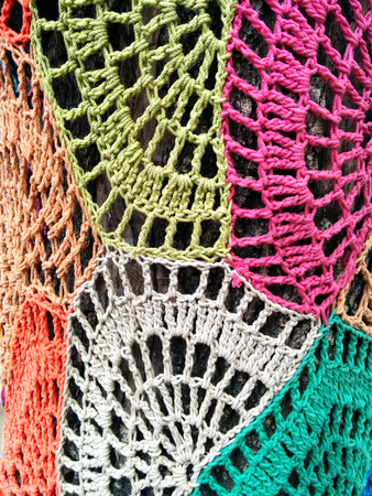 bombing: Yarn bombing. Close-up of tree trunk covered with colorful knits