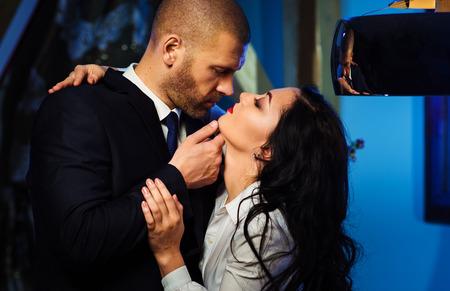 로맨스: 키스 커플. 관능적 인 갈색 머리와 잘 생긴 사업가의 초상화입니다. 사무실 로맨스 개념