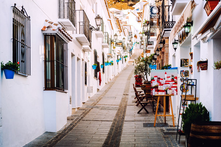 Mijas, Spain- January 05, 2014: Charming whitewashed narrow street In Mijas lined with cafes, restaurants and souvenir shops. Mijas is a lovely Andalusian white village on the Costa del Sol. Spain