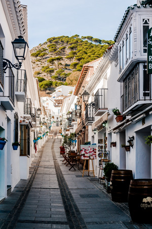 whitewashed: Mijas, Spain- January 05, 2014: Charming whitewashed narrow street In Mijas lined with cafes, restaurants and souvenir shops. Mijas is a lovely Andalusian white village on the Costa del Sol. Spain