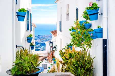 Picturesque street of Mijas with flower pots in facades. Andalusian white village. Costa del Sol. Southern Spain Standard-Bild