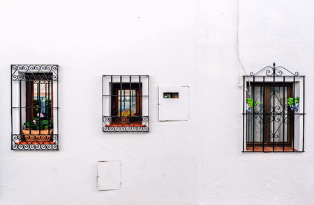 whitewashed: Windows with steel lattice on a whitewashed wall. Andalusian white village. Costa del Sol. Spain Stock Photo