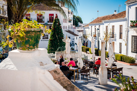 central europe: Mijas, Spain- January 5, 2014: Tourists sitting in a sidewalk cafe on central street of Mijas. Mijas is a lovely Andalusian white village on the Costa del Sol. Spain