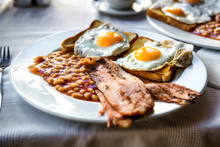 bacon baked beans: Traditional full english breakfast. Sunny-side-up fried eggs, baked beans, bacon and toast