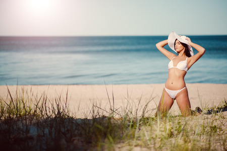 Sexy young brunette in white lingerie and white hat posing on the beach near the sea photo