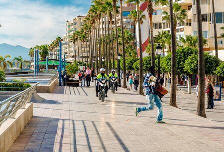street vendor: Marbella Spain January 8 2014: Police on a motorbikes in pursuit of the street vendor. Marbella resort city. Malaga Costa del Sol. Southern Spain
