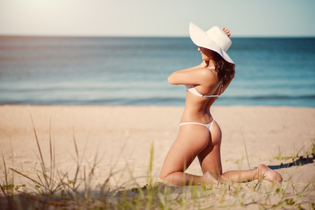 gstring: Sexy young brunette in white lingerie and white hat posing on the beach near the sea Stock Photo