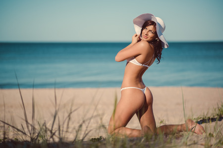 Sexy young brunette in white lingerie and white hat posing on the beach near the sea Stock Photo