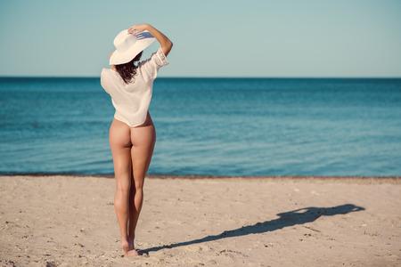 nue plage: Femme nue sexy en chemise blanche et un chapeau posant sur la plage près de la mer Banque d'images