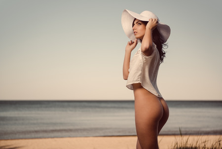 nude outdoors: Sexy naked woman in white shirt and hat posing on the beach near the sea