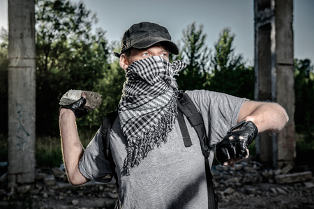 insurrection: Man holding big stone in a hand