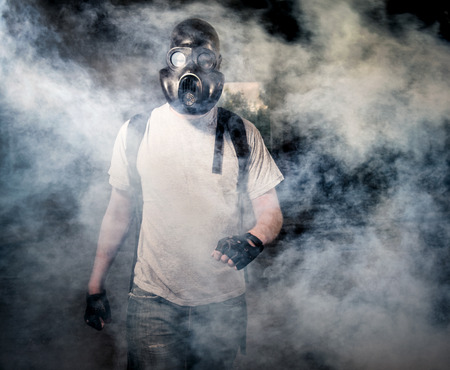 risk of war: Man in a gas mask walking through the smoke Stock Photo