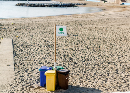 segregate: Four garbage containers for separate types of trash on the beach. Marbella resort city. Province of Malaga Andalusia Costa del Sol. Southern Spain