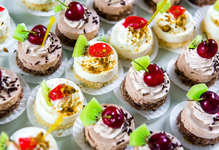 cherry varieties: Delicious small fancy cakes decorated with cherry, kiwi and strawberries