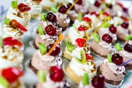 fancy cakes: Delicious small fancy cakes decorated with cherry, kiwi and strawberries