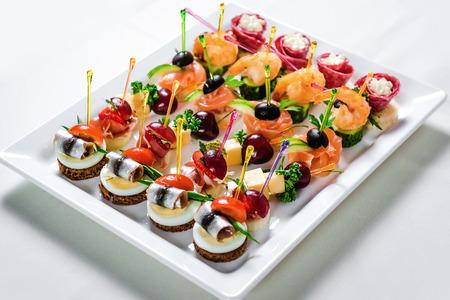 Plaque avec différents fruits de mer et viande canapés. Hareng mariné avec de l'oeuf, le fromage et le cerisier, le saumon, les crevettes avec du concombre et du salami farcis Banque d'images - 41674600