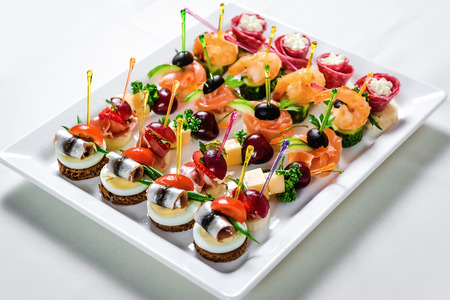 catering food: Plate with various seafood and meat canapes. Pickled herring with egg, cheese and cherry,  salmon, prawns with cucumber and stuffed salami