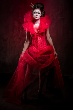 jabot: Red Queen. Woman with creative make-up in fluffy red dress posing indoors