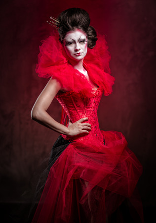 fairytale character: Red Queen. Woman with creative make-up in fluffy red dress posing indoors