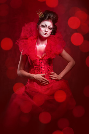 jabot: Red Queen. Woman with creative make-up in fluffy red dress posing over glowing lights background