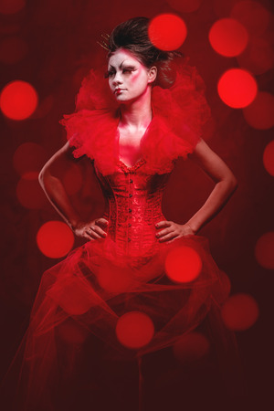jabot: Red Queen. Woman with creative makeup in fluffy red dress posing over glowing lights background